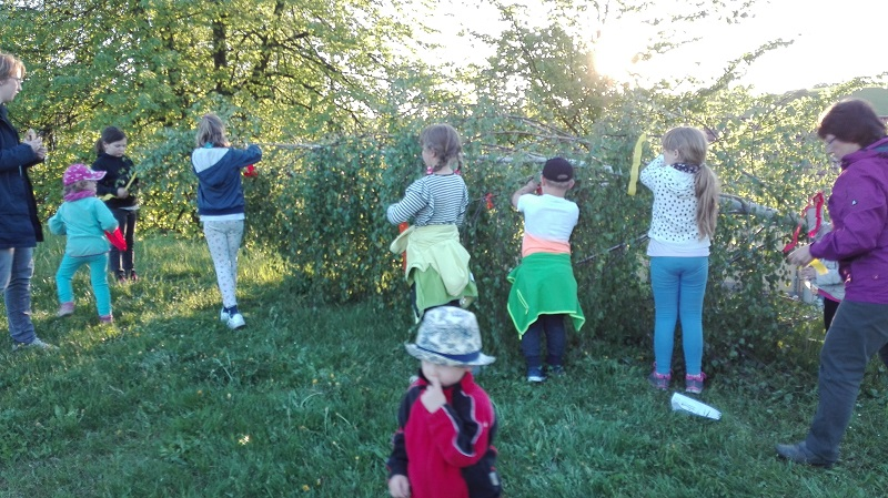 Kinder schmücken den Maibaum