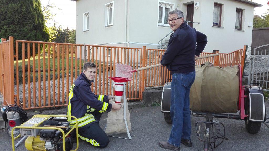 Kameraden der Löschgruppe Hausdorf bei der Demonstration des Sandsackfüllens mit Pylonen